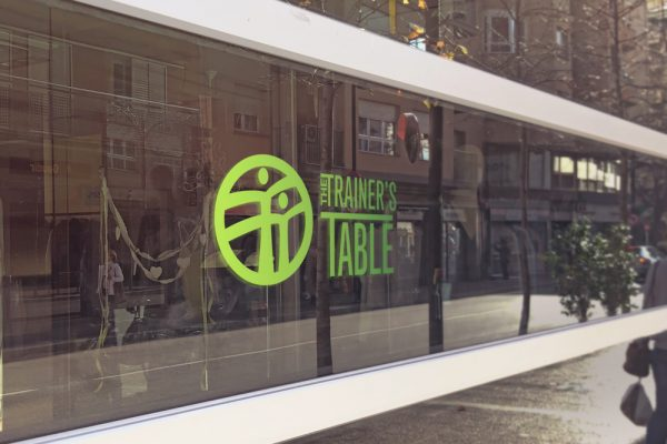 Trainer's table logo design in gradient paint on glass windows